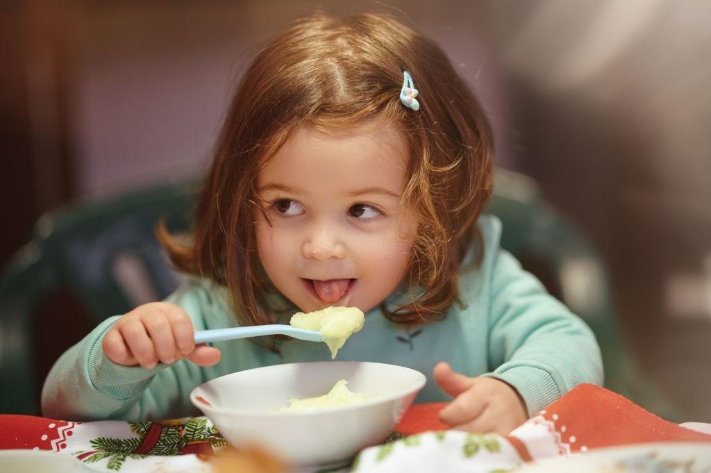 Niña comiendo puré de patatas para bebés