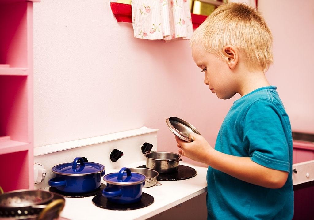 Niño jugando a las cocinitas de juguete