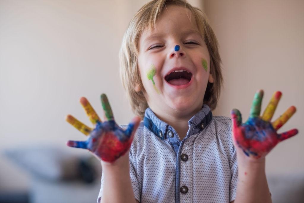 niño jugando con pintura de dedos