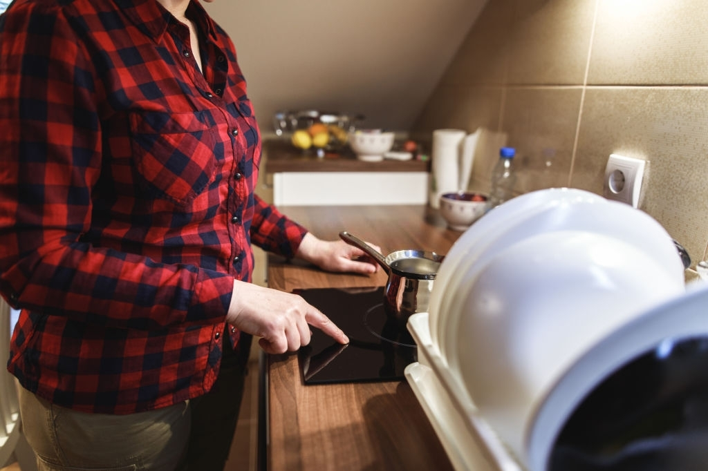 Mujer cocinando en placa de inducción